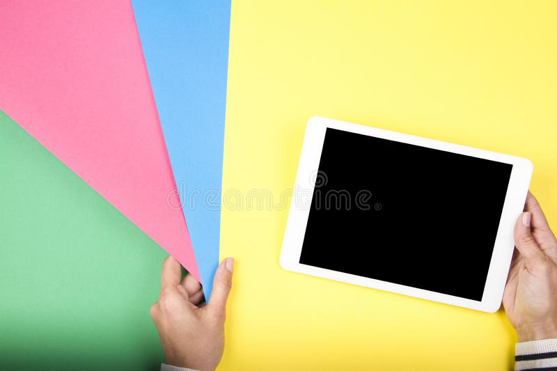 Woman hand holding colorful paper samples and tablet computer royalty free stock photography