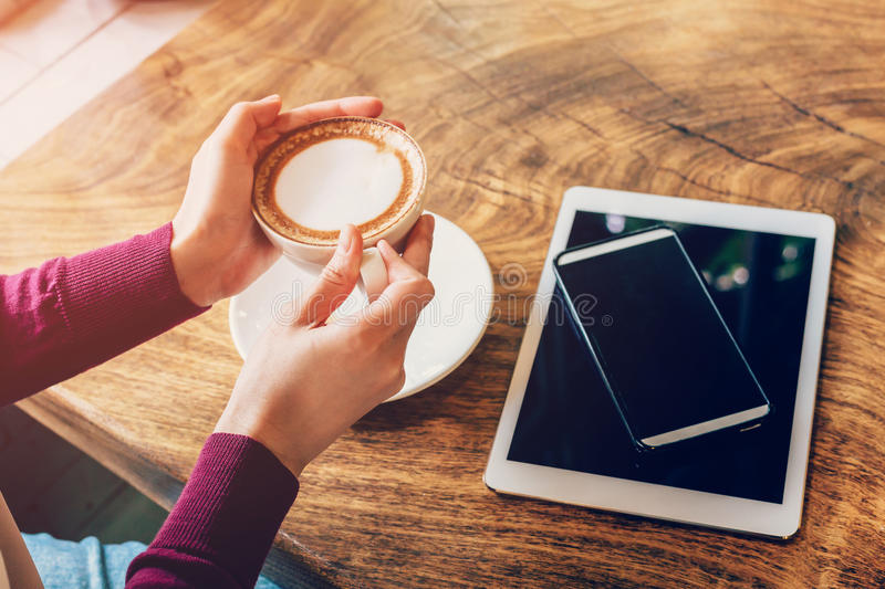 Woman hand holding cup coffee in cafe with smartphone and tablet royalty free stock image