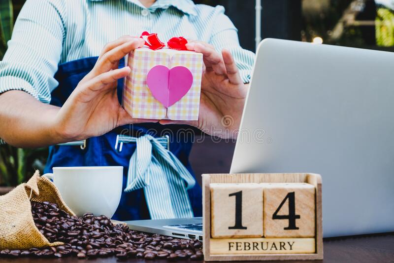 Woman hand holding gift box with laptop, 14 February wooden calendar, coffee cup and coffee beans. Valentine day concept.  royalty free stock photography