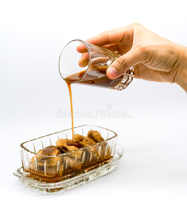 Woman hand holding glass adding Coconut-Caramel Sauce on top of stock photo