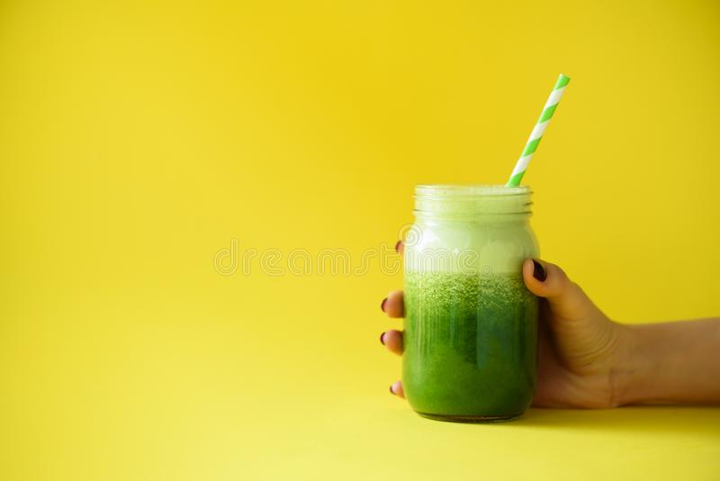 Woman hand holding glass jar of green smoothie, fresh juice against yellow background. Healthy beverage, vegan, vegetarian concept royalty free stock images