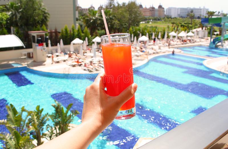 Woman hand holding glass with a layered cocktail on pool background. Summer travel, vacation, all inclusive concept royalty free stock photos