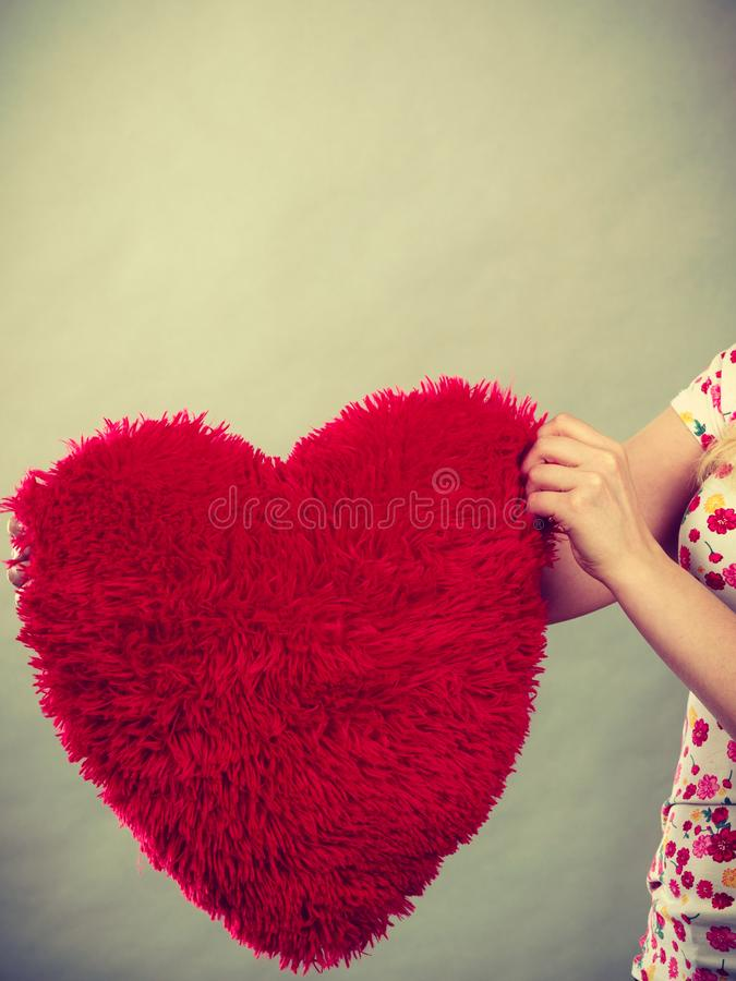 Woman hand holding heart shaped pillow stock image
