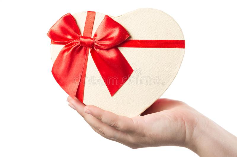 Woman hand holding heart shaped present box with red ribbon isolated on white background. royalty free stock photography