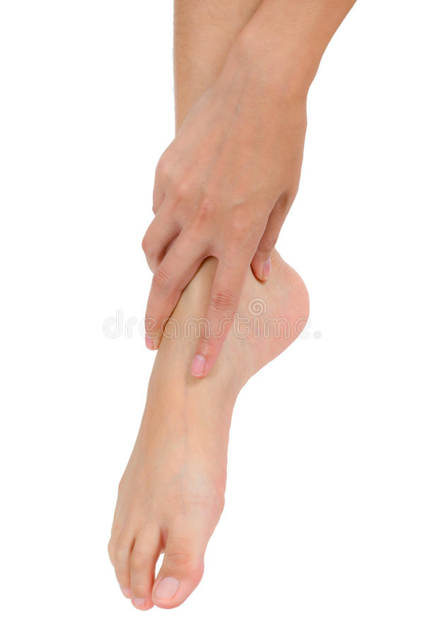 Woman hand holding her beautiful healthy foot and massaging ankle in pain area. royalty free stock photography