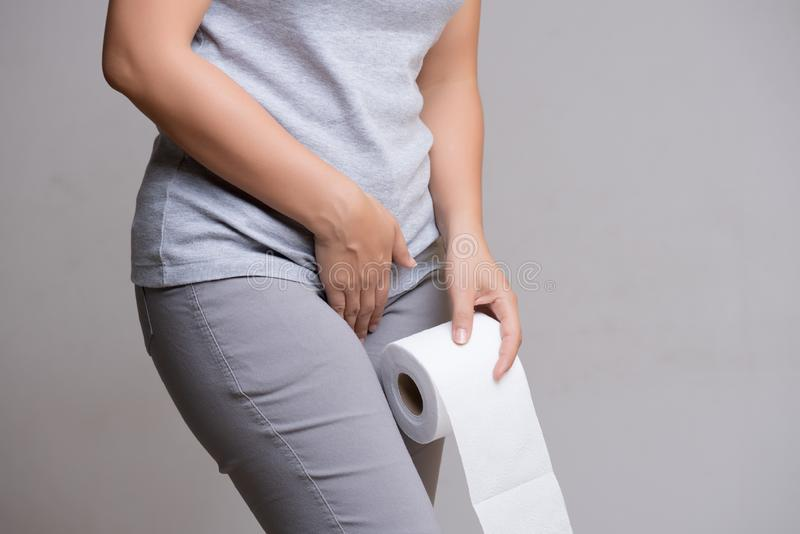 Woman hand holding her crotch lower abdomen and tissue or toilet paper roll. Disorder, Diarrhea, incontinence. Healthcare concept stock photos