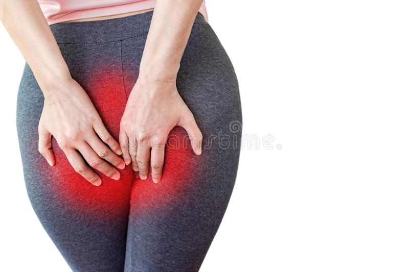 Woman hand holding her painful butt caused by hemorrhoids. Isolated on white background royalty free stock photo