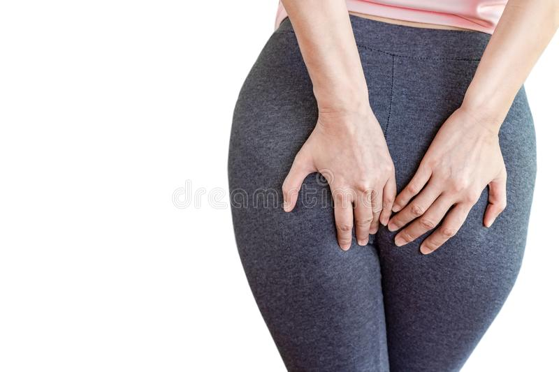 Woman hand holding her painful butt caused by hemorrhoids. Isolated on white background stock photography