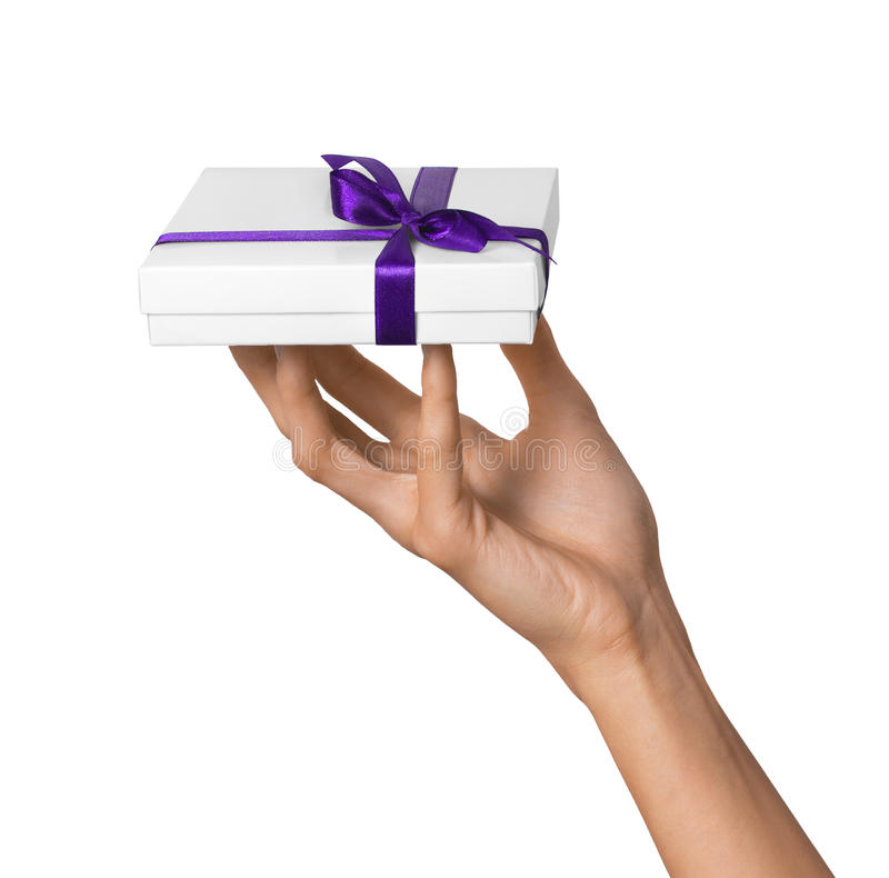 Woman Hand holding Holiday Present White Box with Purple Ribbon. Woman Hand holding Present White Box with Purple Ribbon royalty free stock images