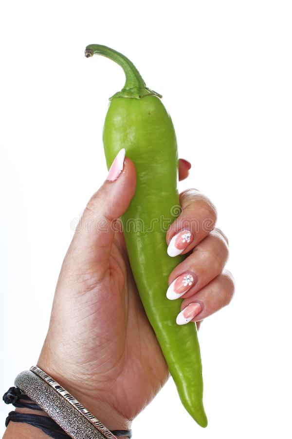 Woman hand holding hot strong green pepper on isolated white cutout background. Studio photo with studio lighting easy. Woman hand holding green pepper on stock image