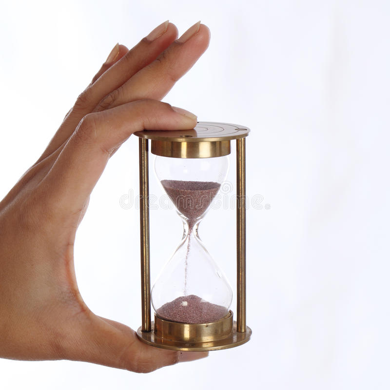 Woman hand holding a hourglass stock photo