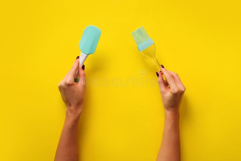 Woman hand holding kitchen utensils on yellow background. Baking tools - brush, whisk, spatula. Bakery, cooking, healthy homemade stock photo