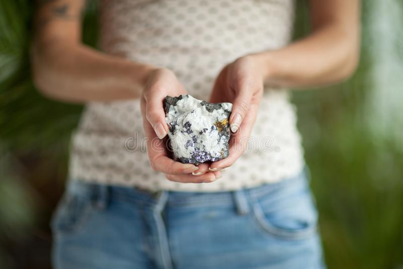Woman hand holding little crystal mineral rock, sensual studio shot with soft light stock photography