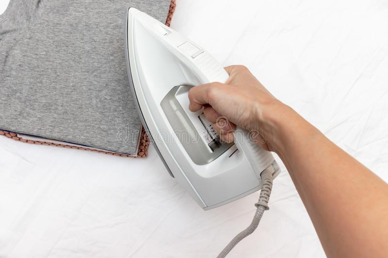 Woman hand holding a modern electrical white iron, a stack of clothes on background, close up view - ironing, laundry and stock images