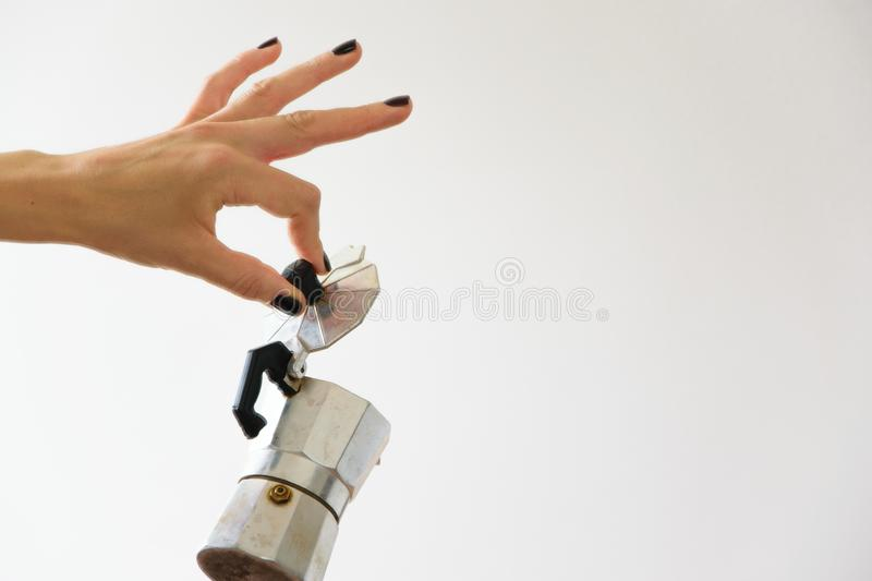 Woman hand holding a moka - traditional italian coffee maker. White background and copy space royalty free stock image