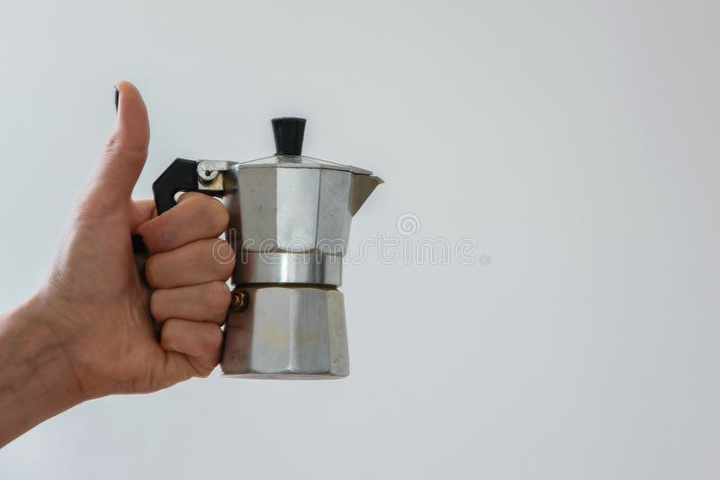 Woman hand holding a moka - traditional italian coffee maker. White background and copy space royalty free stock photo