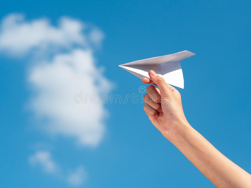 Woman Hand holding paper rocket with blue sky background. freedom concept stock photography