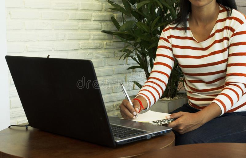Woman hand holding pen with notebook and using laptop at coffee cafe for lifestyle technology. Concept royalty free stock image