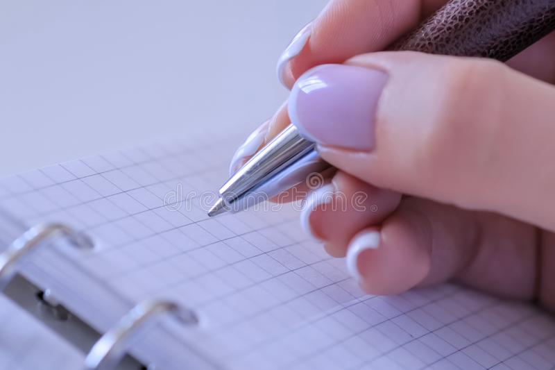Woman hand holding pen and preparing to write to do list in notebook organizer stock image