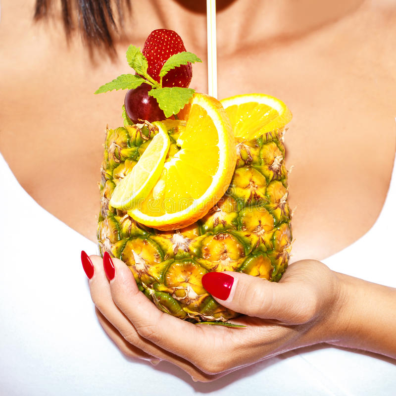 Woman hand holding pineapple cocktail closeup royalty free stock photography