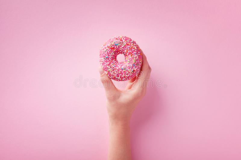 Woman hand holding pink donut or doughnut on pastel background. Flat lay royalty free stock images