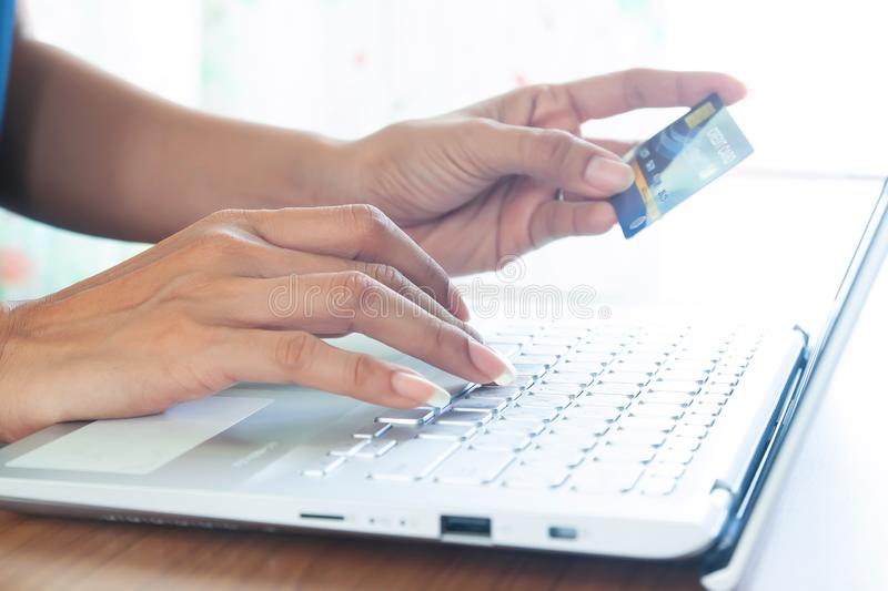 Woman hand holding plastic credit card and using laptop computer. Online shopping, paying, buying, e-payment and technology royalty free stock images