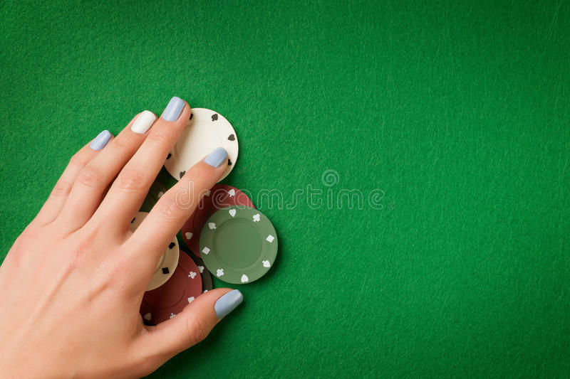 Woman hand holding poker chips on green casino felt background. Gambling theme image with copy space royalty free stock images