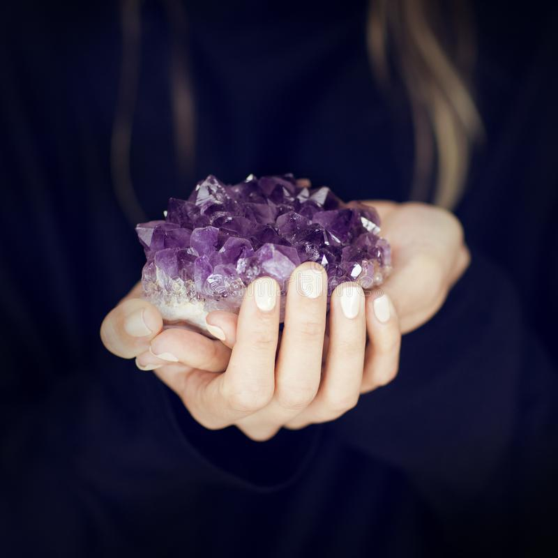 Woman hand holding purple crystal, amethyst, melancolic sensual studio shot stock photography