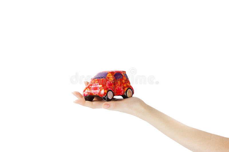 WOMAN HAND HOLDING A RED CAR ISOLATED ON WHITE royalty free stock photo