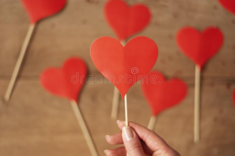 Woman hand holding red paper heart. Many hearts on a wooden background in defocus. Valentine`s Day concept royalty free stock images