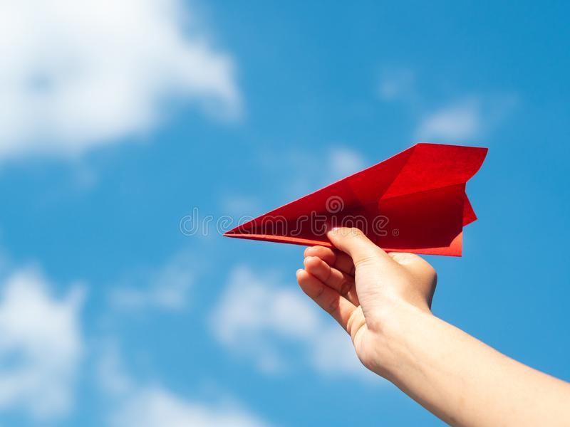 Woman Hand holding red paper rocket with blue sky background. freedom concept royalty free stock images