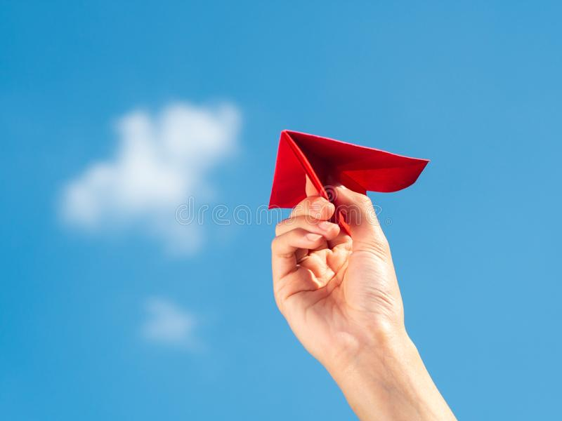 Woman Hand holding red paper rocket with blue sky background. freedom concept stock photo