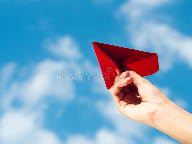 Woman Hand holding red paper rocket with blue sky background. freedom concept royalty free stock photography