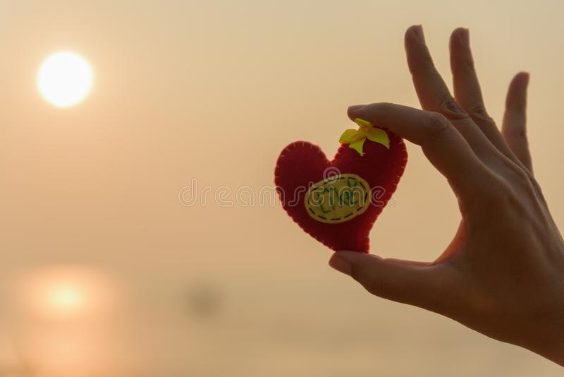 Woman hand holding a red pillow in heart shaped on the beach royalty free stock photography