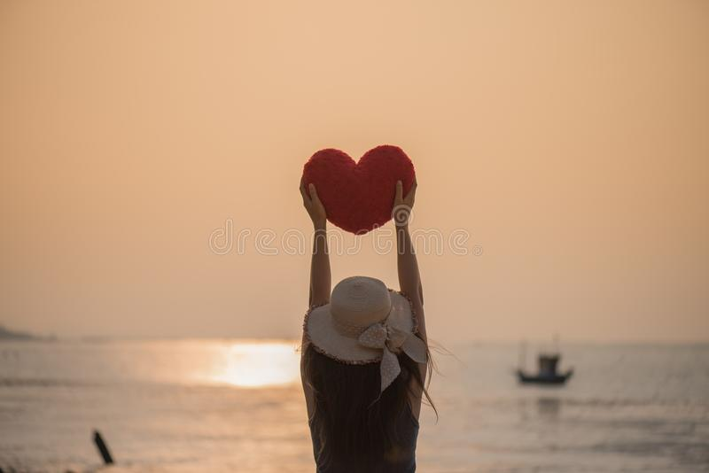 Woman hand holding a red pillow in heart shaped on the beach. During sunset for Valentines day and love concept royalty free stock images