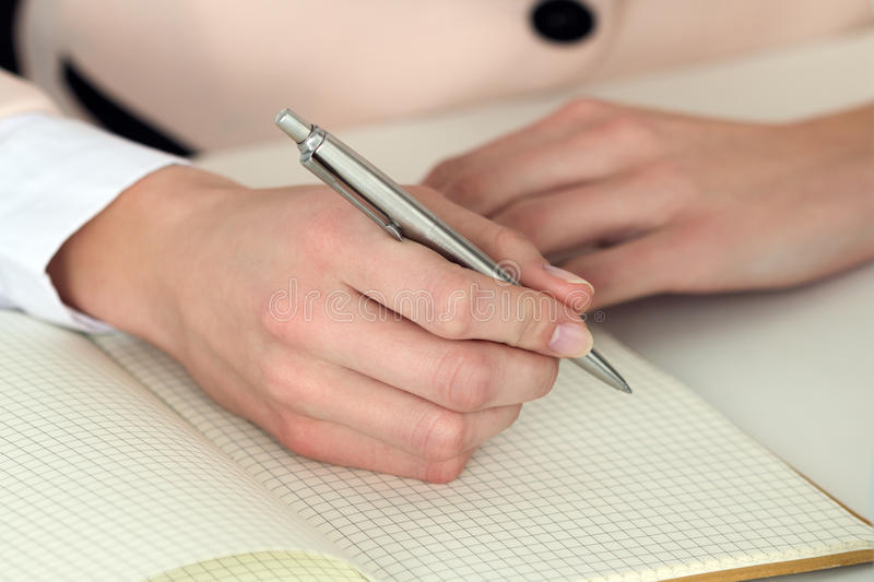 Woman hand holding silver pen ready to make note in opened notebook royalty free stock photos