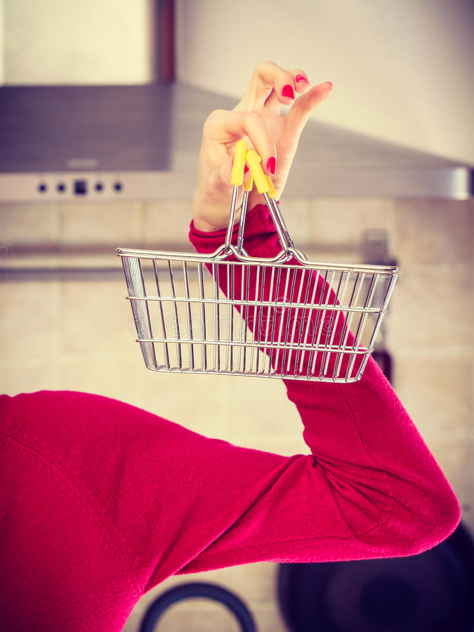 Woman hand holding small tiny shopping basket royalty free stock image