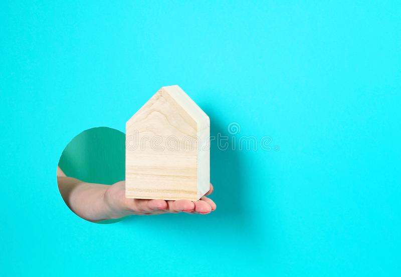 Woman hand holding small toy house. Taking loan, insurance, buying, renting house concept royalty free stock photos