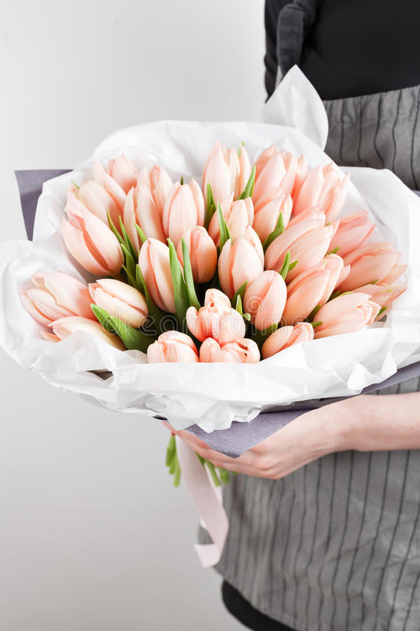 Woman hand holding soft pink tulips flowers on white background. bouquet decorated with kraft paper royalty free stock photography