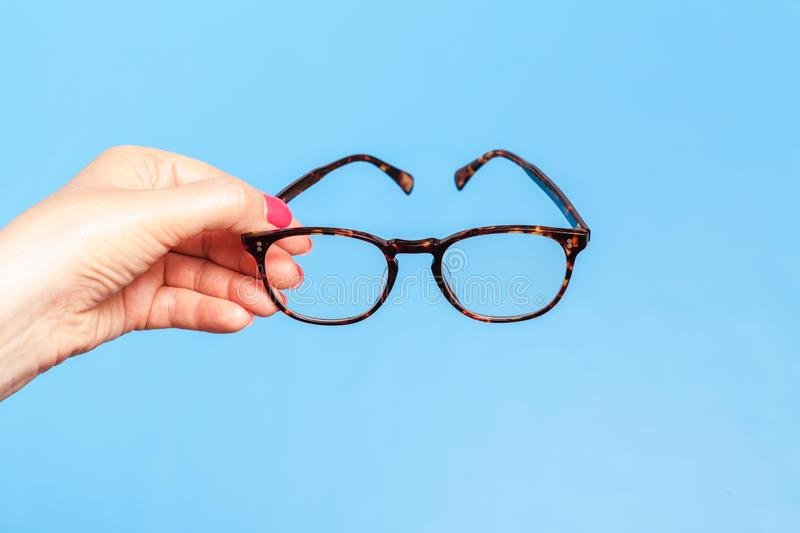 Woman hand holding spectacles on blue background stock images