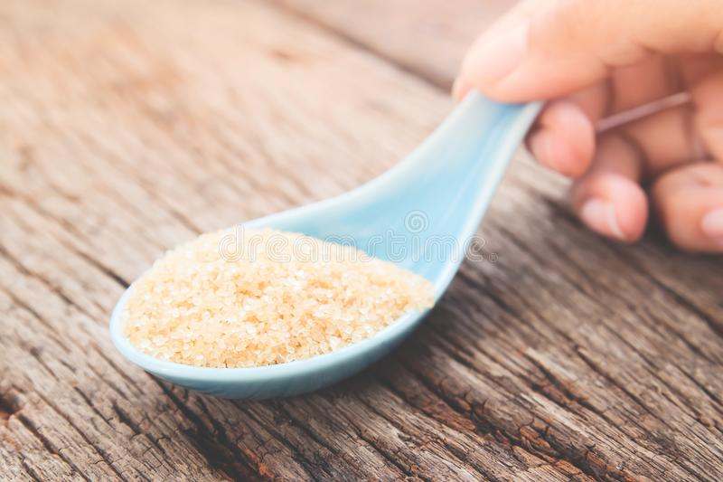 Woman hand holding spoon with brown sugar, Unhealthy and Diet concept. Close up stock photography