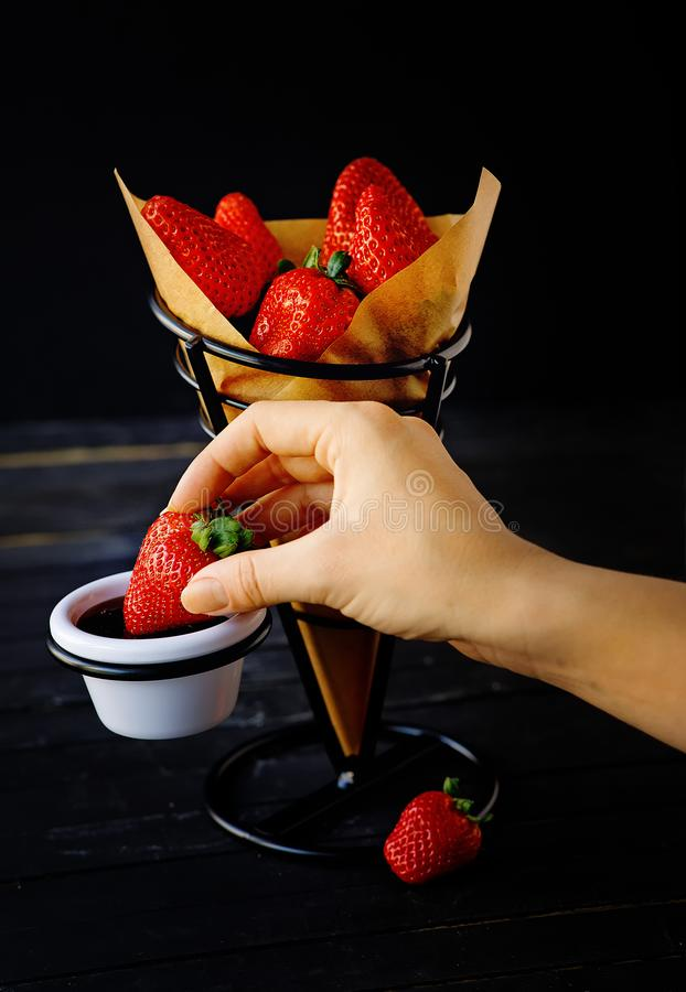 Woman hand holding a strawberry and dipping chocolate. Dessert concept on a fancy support. Isolated on the dark background royalty free stock photos