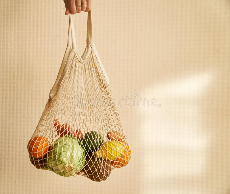 Woman hand holding a string shopping bag with vegetables, fruits in warm earthy tones, zero waste stock image