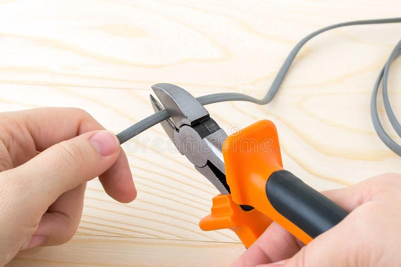 Woman hand holdins a metall side cutters with orange black rubber handles and cutting a wire over a rough wooden background. royalty free stock image