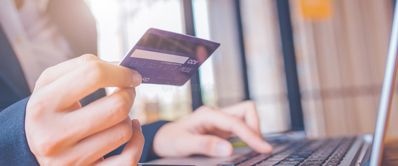 Woman hand holds a blue credit card.And are using a laptop computer.Web banner royalty free stock photography