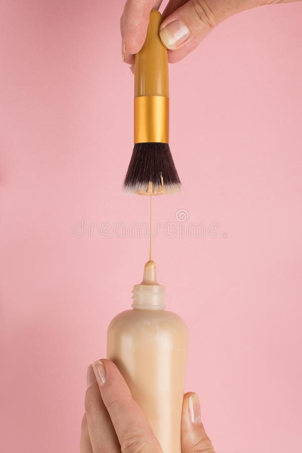 Woman hand holds a bottle of foundation, puts on a brush, on a pink background. Makeup artist work concept, copy space. Woman hand holds a bottle of foundation royalty free stock photo