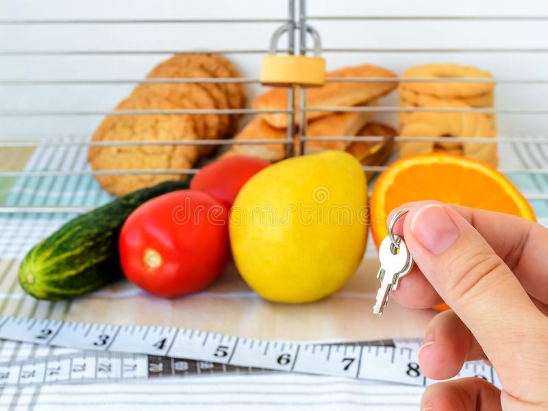 Woman hand holds the key of cell with cookies. Cookies are in the cage locked with padlock. Vegetables, fruits and measuring tape royalty free stock photography