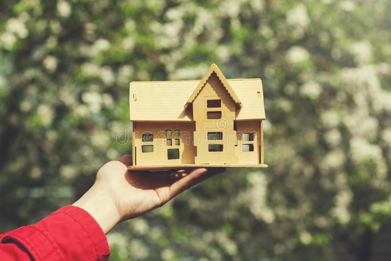 Woman hand house model. With flowers in nature royalty free stock images