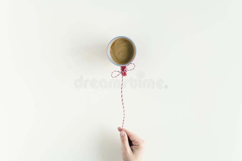 Woman hand with Inflatable air flying balloon made from cup of coffee hanging on a red white string or twine tied in a bow. royalty free stock image