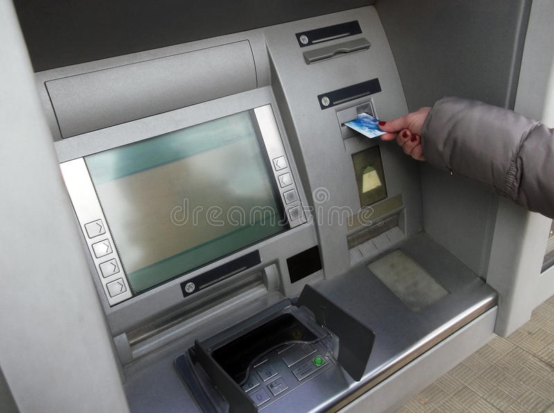 Woman hand inserting ATM card into bank machine to withdraw money. stock photos